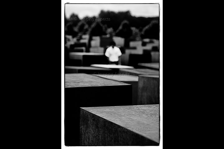 An out of focus man stands in the middle of the Memorial to the Murdered Jews of Europe in Berlin, Germany.