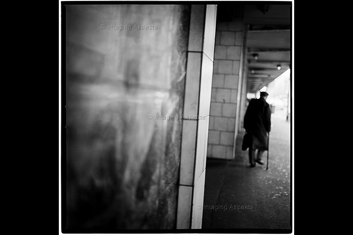 Old man with walking stick walks away from Spencer Street Railway Station (now Southern Cross Station) in Melbourne, Australia.