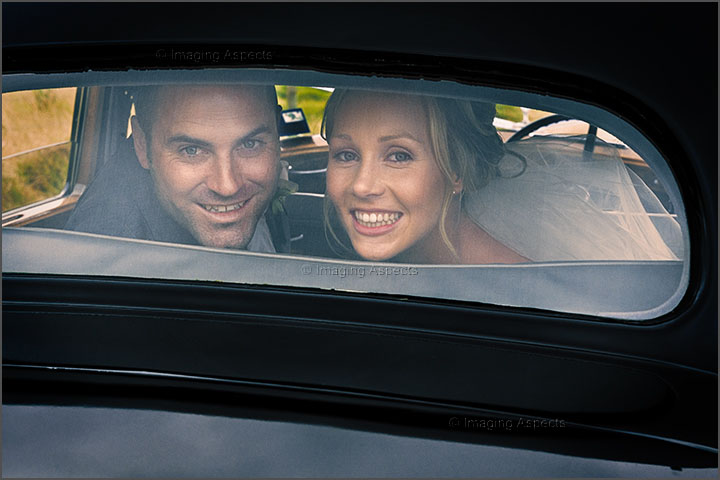 Newlyweds smile at the camera through the rear window of their Bentleigh Limousine.